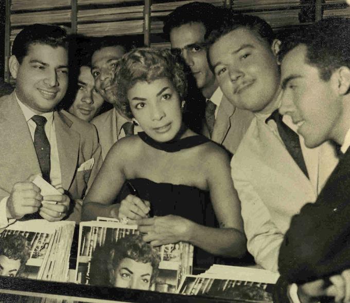 Lançamento do disco Canção do Amor Demais. Jornais da época noticiam que a cantora foi homenageada com um coquetel na filial de Copacabana de O Rei da Voz