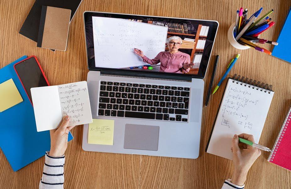 imagem ilustrativa de estudante fazendo aula de graduação a distância de frente para o computador e tomando notas