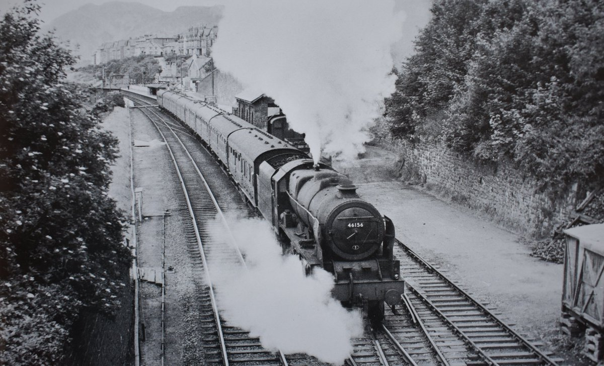 Rebuilt Royal Scot 46156 'The South Wales Borderer' makes a rapid departure from #Penmaenmawr with a semi-fast express for #Holyhead. Date: Unknown.  Photo by Keith Smith. #steamlocomotive #NorthWales #expresstrain pic.twitter.com/WRtCCgxoQU