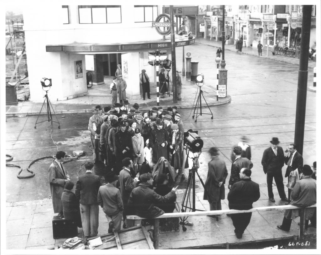 How to make a crowd seem bigger than it is in sunny Middlesex! Hitchcock (leaning on rail) directs a crowd scene for Sabotage (1936) on the Gaumont British lot at Eastcote Lane in Northolt. The UK copyright on this photograph expired at the end of 1936, but the final form of the contents of the film camera seen in it remain protected until the end of 2065 in the UK, and 2031 in the US.