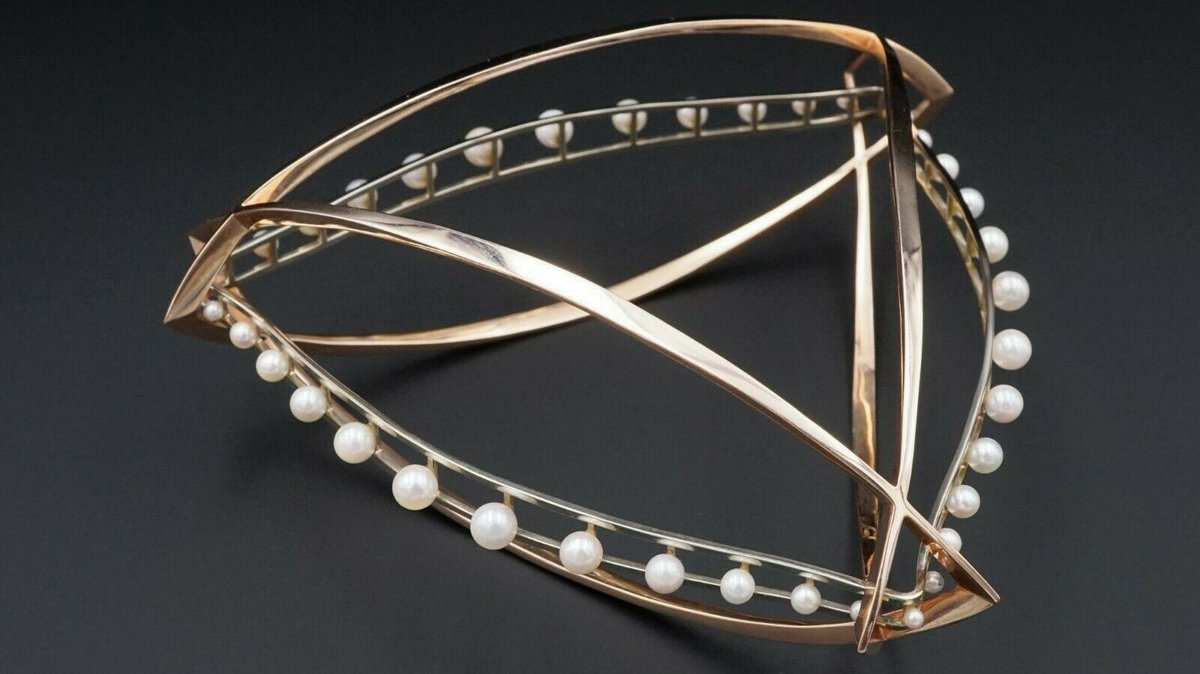 This #bracelet features an incredible #abstractdesign. 3 #rosegold marquise shaped sections intertwine to form a #triangle, and inserted into this form is a #whitegold triangle that is set with graduated #pearls. #signedjewelry #designerjewelry #vintage