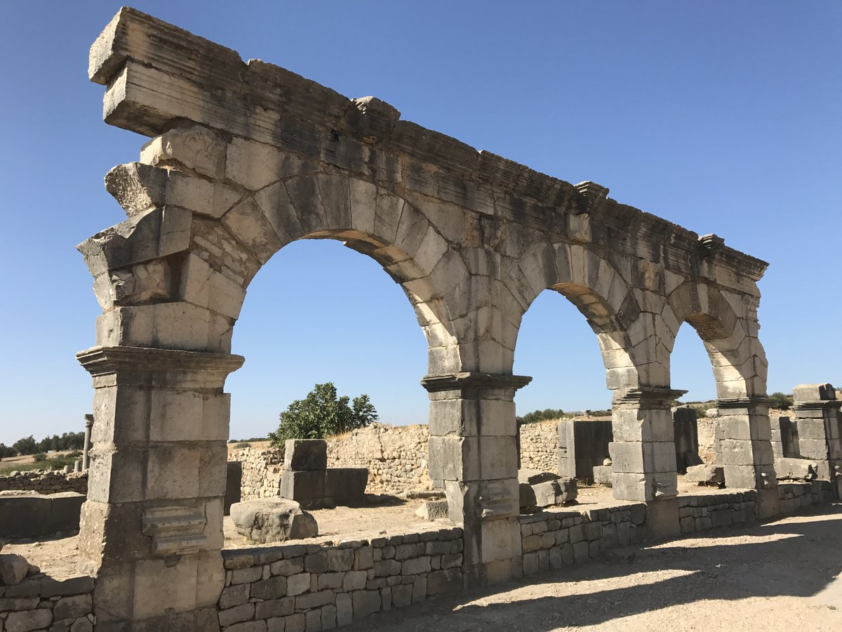 Remains of the Berber/Roman city of Volubilis, Morocco, including the Arch of Caracalla and a Temple dedicated to the Capitoline Triad of Jupiter, Juno, and Minerva. The city was patronized by the Kings of Mauretania and later by the Roman Empire (2017)