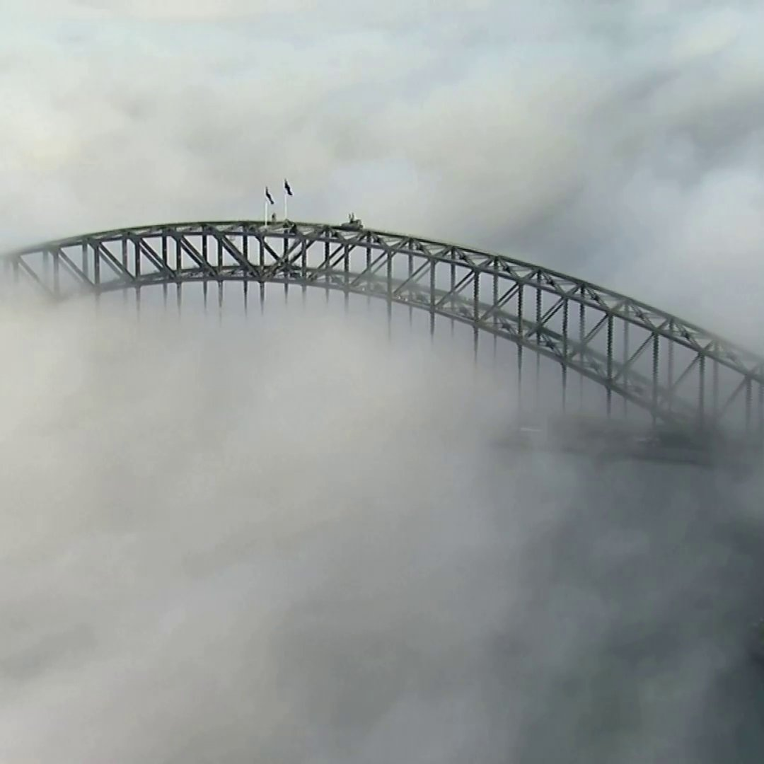 WATCH: Fog shrouded the Sydney Harbour Bridge and parts of the city on Tuesday. The Australian and New South Wales flags were visible atop the iconic landmark with some skyscrapers peaking out of the thick blanket of fog.