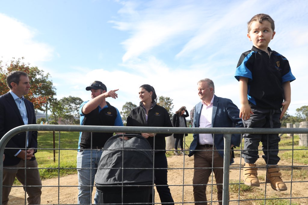 Lane Corby looks out over the fence gate of his fire affected farm while his parents Tamara and Craig talk to Opposition leader Anthony Albanese and Jim Chalmers during campaigning with the Eden-Monaro candidate Kristy McBain today  near Cobargo #AusPolpic.twitter.com/FeTqyJOPU5