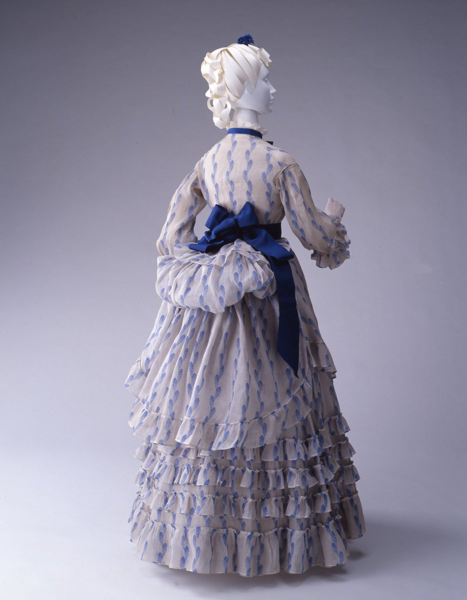 A blue and white china #shepherdess of a dress, gauzy ruffles and satin #ribbons tweaked and plumped into place. You can almost feel a summer breeze lifting the frills at the hem. Mid #1870s #thekyotocostumeinstitute #fashionhistorypic.twitter.com/XZaxhrkKbN