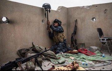 جندي من الشرطة الاتحادية يقوم برفع خوذته لكشف موقع قناص داعشي اثناء حرب الموصل -٢٠١٧م.