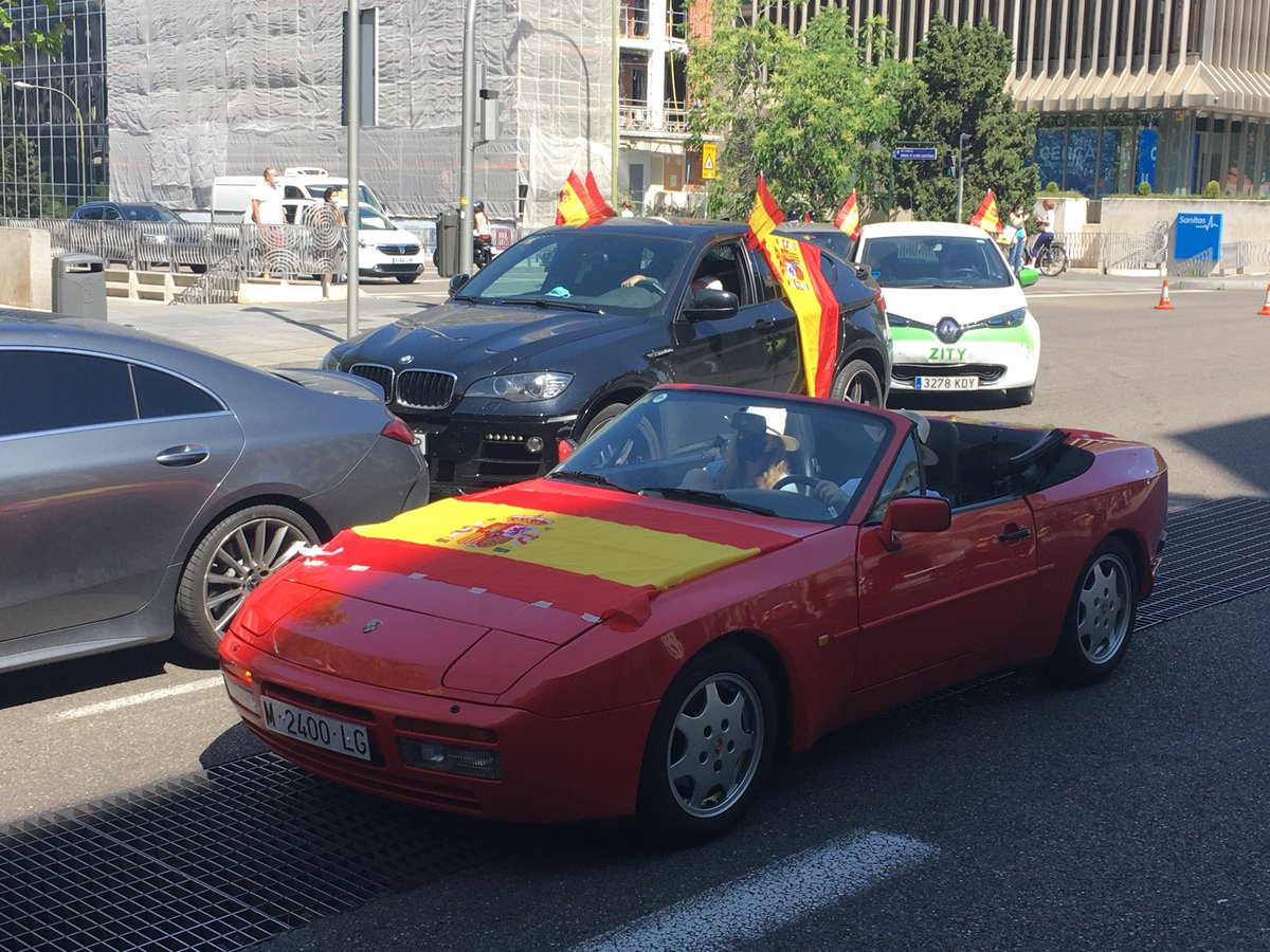 Organized by Vox, today's anti-goverment, drive-by rally has taken over central Madrid. This couple in their sports convertible know how to protest in style.<br>http://pic.twitter.com/L5ZDh1J2vF