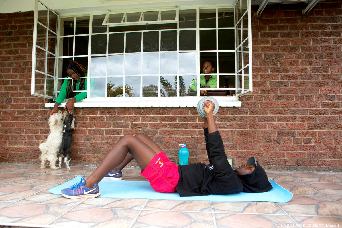 "Fifteen-year-old Tapfuma in Zimbabwe exercises outside while his siblings play with the family dogs. His father, Tsvangirayi, says that staying home together has been ""a great opportunity to reflect on so many things."" Keeping close with family can mean staying #HealthyAtHome."