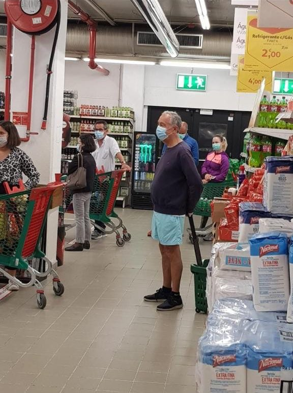 What makes this photo so amazing is that it looks so ordinary. The man in the shorts waiting in line in this shop in Portugal is the President.