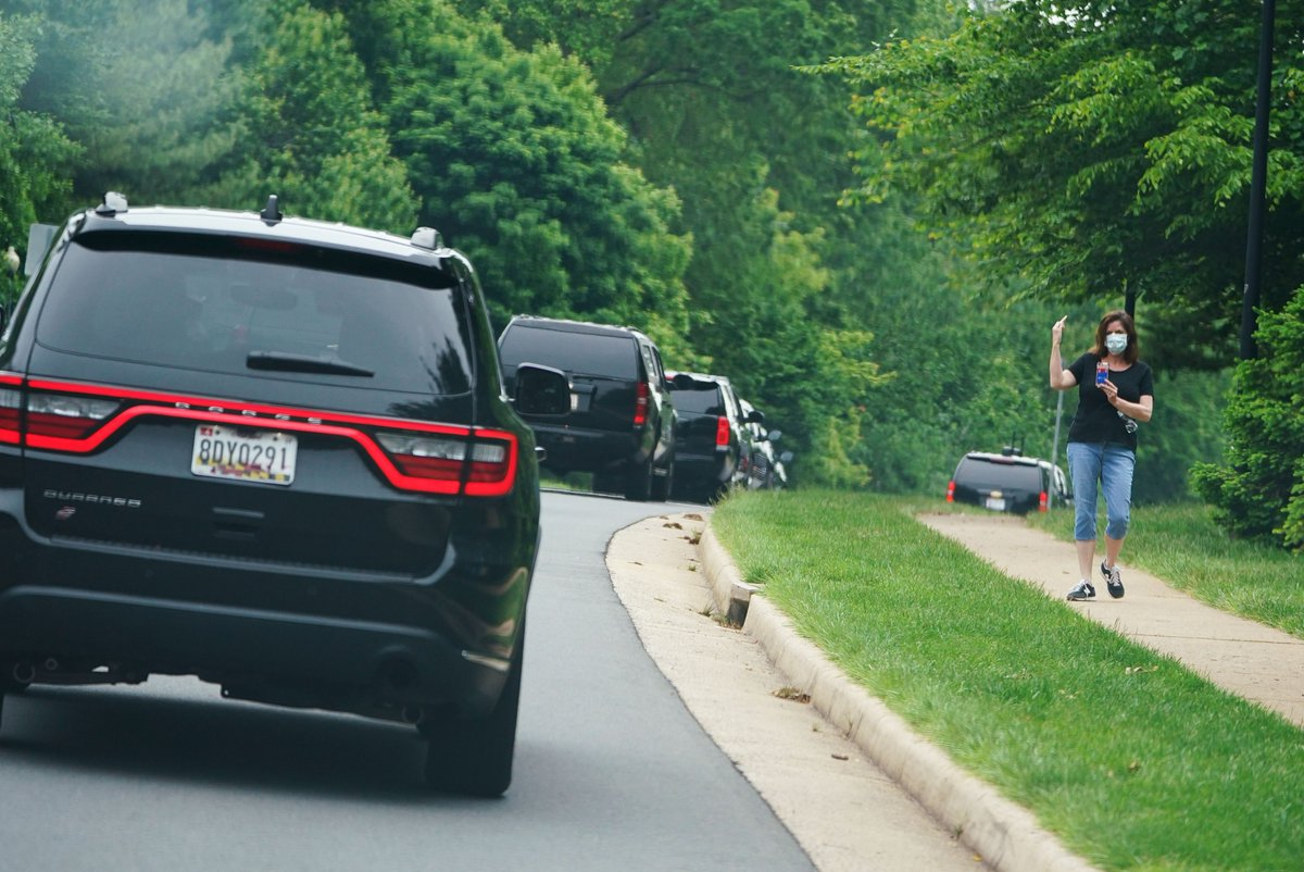 A woman raises her middle finger at Trumps motorcade as it passes through Sterling, Virginia, on its way to the Trump National Golf Course. (Mandel Ngan/AFP)