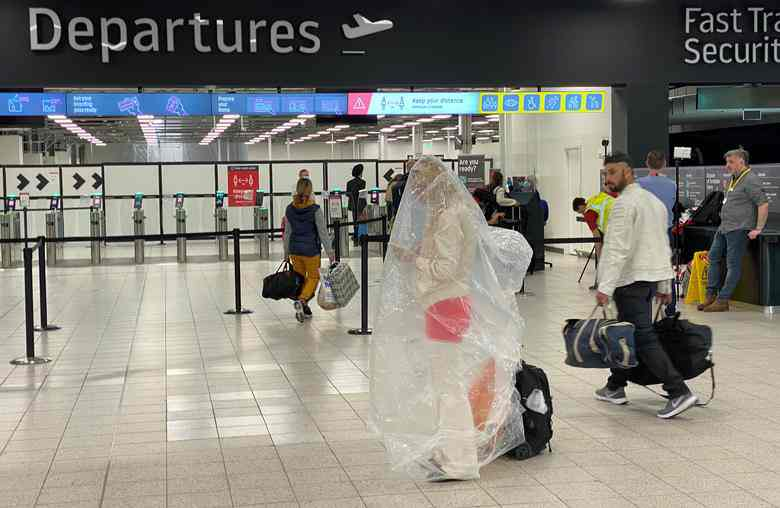 A passenger covered with a plastic bag is seen at Luton Airport in #Britain. pic.twitter.com/Cs7FUXCvUD