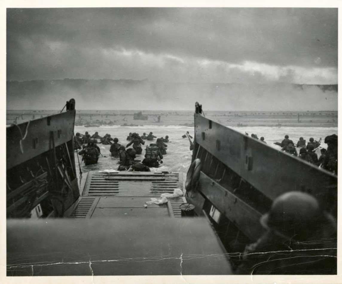 """Soldiers giving the ultimate sacrifice on this day in 1944 captured by this photo by Robert F. Sargeant titled """"Into the Jaws of Death."""" It depicts allied troops leaving their Higgins boat and storming into the water of Omaha Beach in the invasion of Normandy. https://t.co/YY8LHjr1bG"""