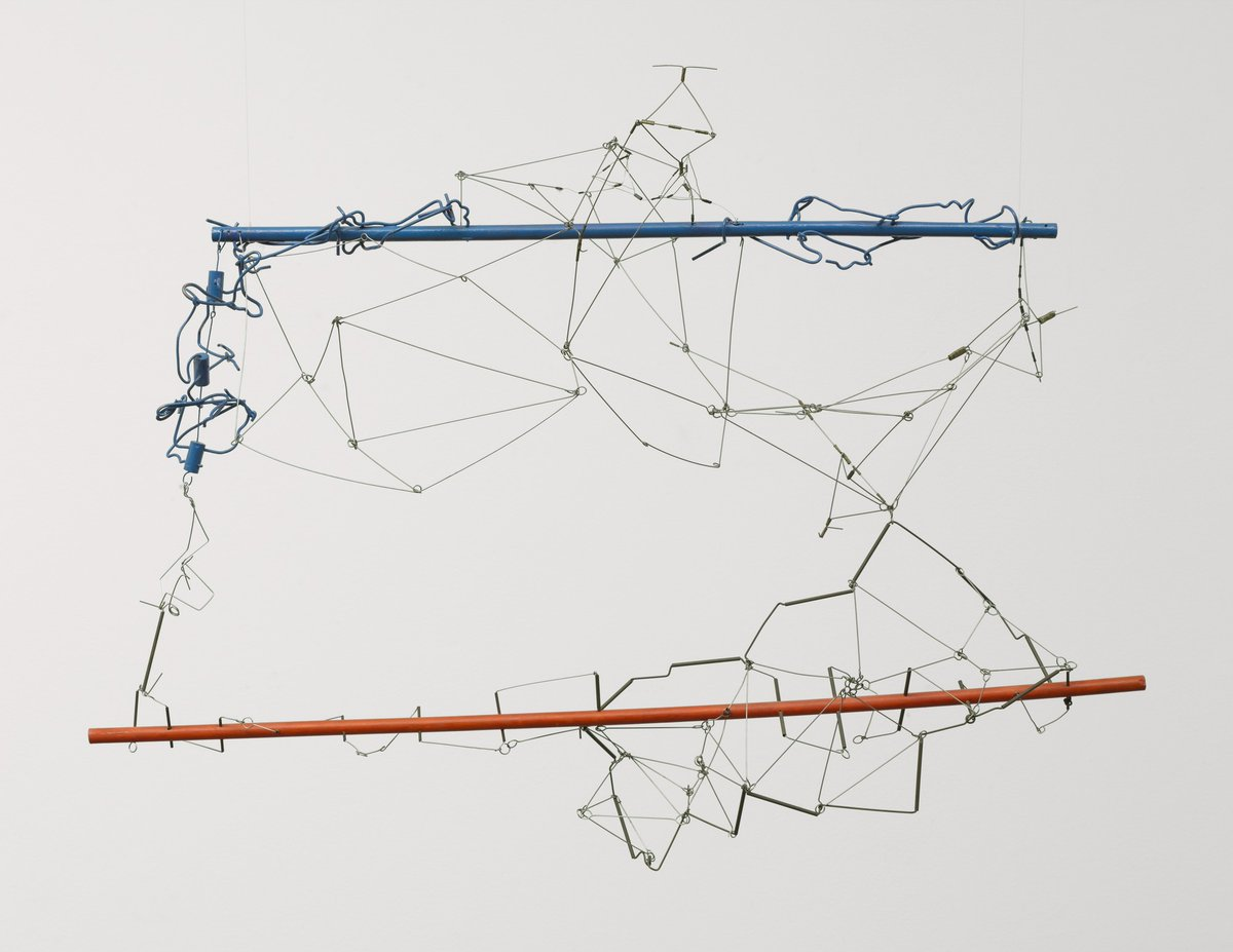 A hanging sculpture with a horizontal dowels creating the shape of a rectangle - the top dowel is blue and the bottom one is red.There are wires twisted around these dowels moving in and out of the space.