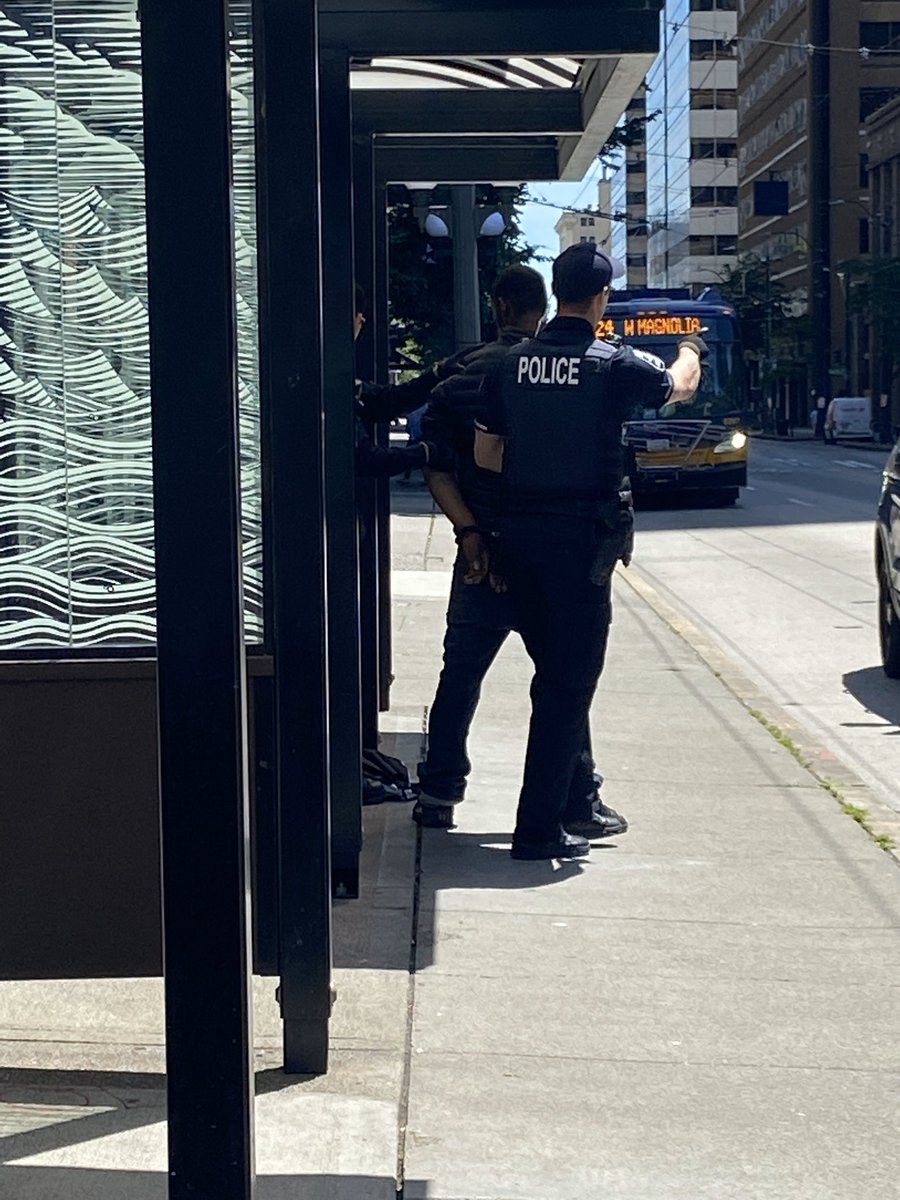 """I was at a bus stop in downtown #Seattle today and 2 cops pulled up and asked one black man about his """"suspiciously"""" large suitcase. Then, they harassed another black man sitting at another bench, cuffed, searched, and arrested him. All in 3 mins. Cops are terrorists pass it on. pic.twitter.com/B2TpgDnh9P"""