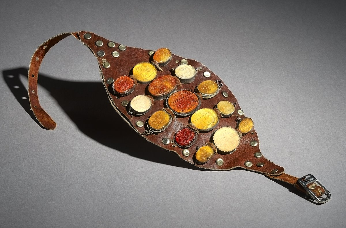 An Iranian wrestler's leather armband (bazuband) with 15 red, orange and yellow amulets inscribed with verses from the Qur'an.