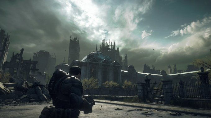 The image is a screenshot from Gears of War: Ultimate Edition in which we see Marcus Fenix in the left of the frame as he approaches a domed building in an otherwise ruinous city.