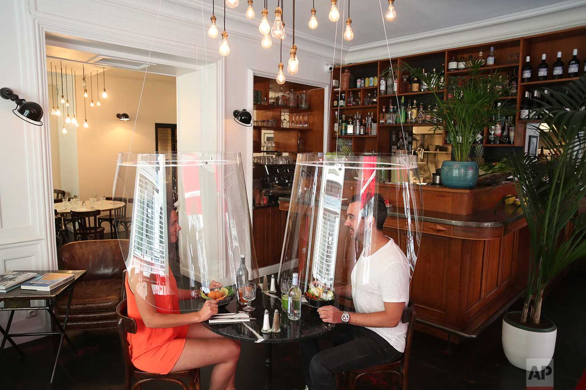 A man and a woman demonstrate dining under a plastic shield in a Paris restaurant on Wednesday, May 27, 2020. As restaurants in food-loving France prepare to reopen, some are investing in lampshade-like plastic shields to protect diners from the virus. | Photo Thibault Camus