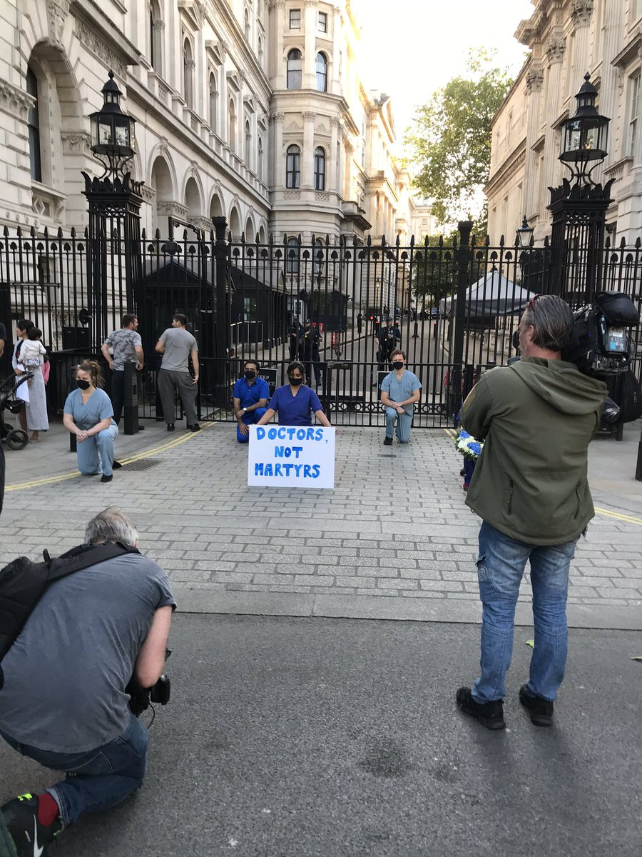 """as 8pm clap happened across the country, these doctors silently took a knee outside downing street and displayed a sign stating """"doctors not martyrs"""". it's reported that over 200 nhs staff have died from coronavirus so far. https://t.co/TppKSiNo5H"""