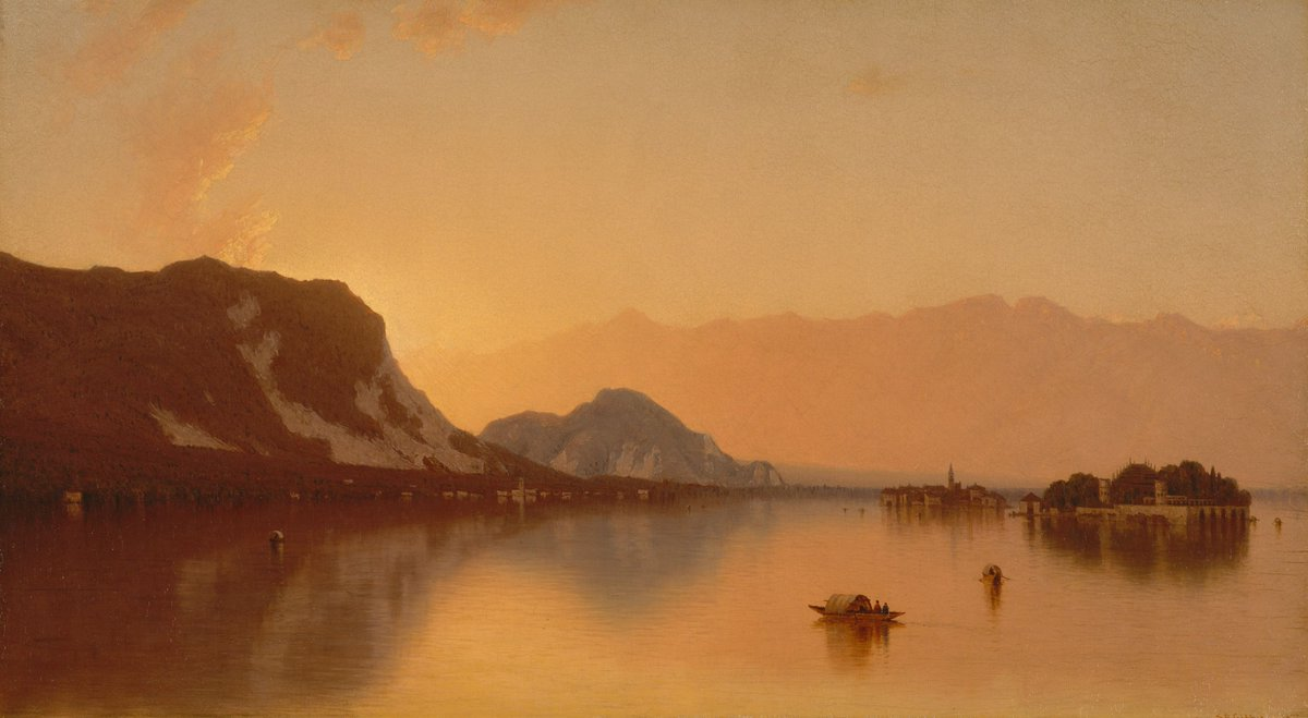 A bright orange sunset casts its light across a mountainous lake scene.