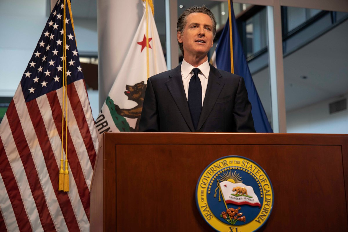 Governor Gavin Newsom stands at a podium speaking