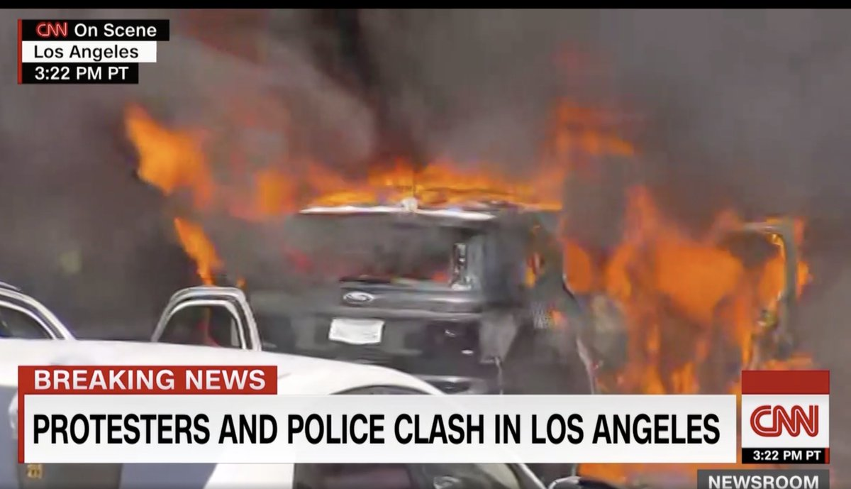 A police car appears to be on fire in Los Angeles. Police officers are holding back a line of demonstrators to prevent them from getting close to the car. https://t.co/B9s2gmaGal https://t.co/gISAvzpsC1