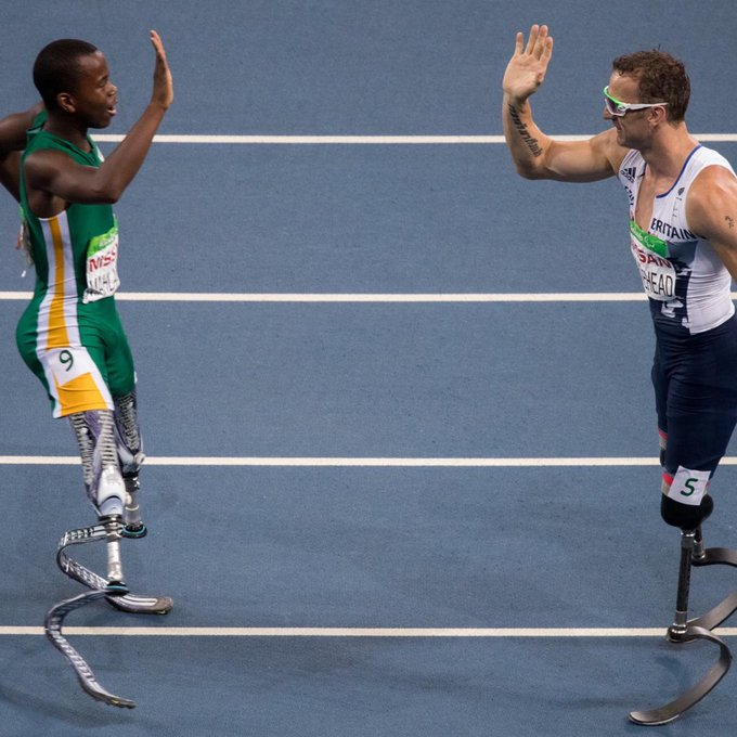 Two double-amputee male sprinters high-five each other