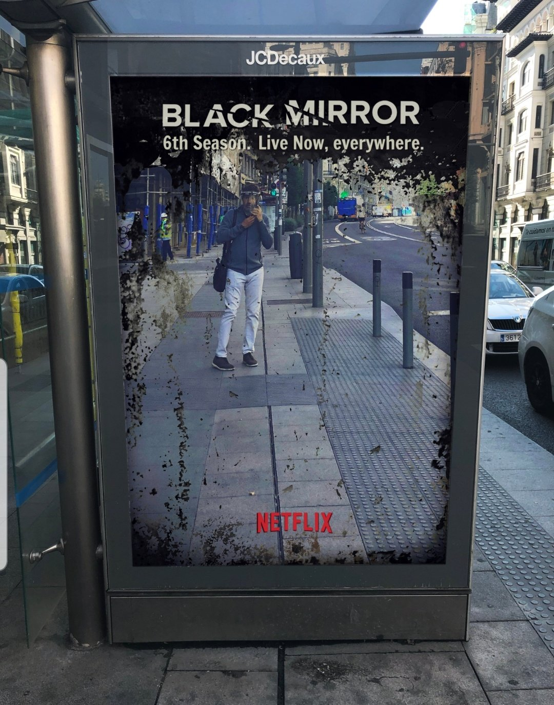 An image of a bus shelter ad. The ad is a mirror with black around the edges. At the top of the mirror it says