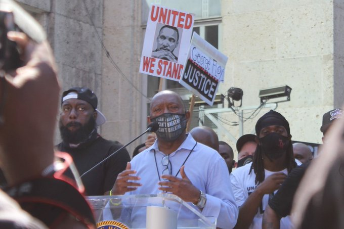 """Mayor Turner speaks for the podium while protesters hold up signs behind him that say """"United we stand"""" and """"George Floyd Justice"""""""