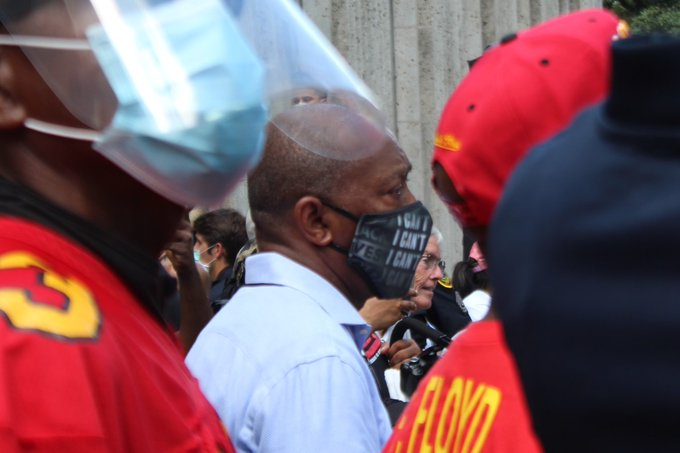 """Mayor turner wears a mask that says """"I can't breathe"""" while standing next to one of George Floyd's family members wearing his yates high school football jersey"""