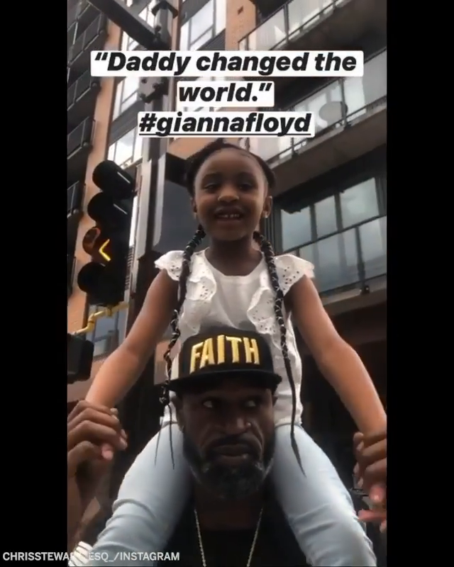 "Stephen Jackson holding up George Floyd's daughter, Gianna, as she says ""Daddy changed the world."" (via chrisstewart_esq_/Instagram)"