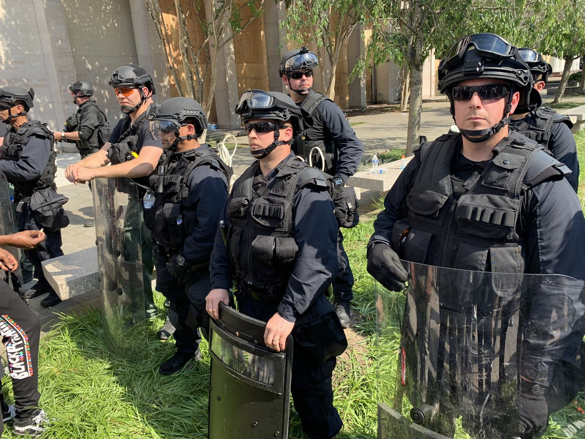 "Shift change: National guard has been replaced with a different unit. One officer identified himself to protestors as being with ""DOJ"", another said he was from California, and one has a Bureau of Prisons patch on his vest. No name plates."