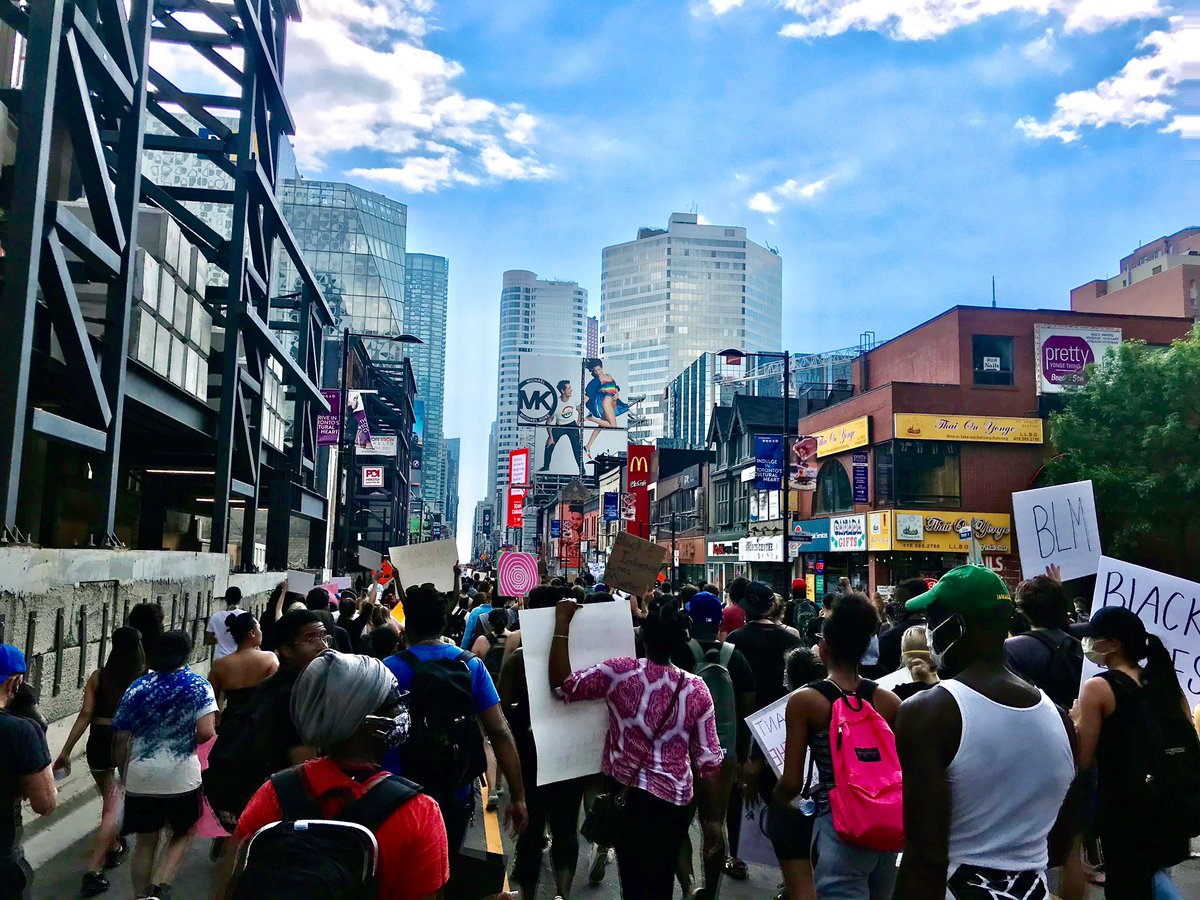 A powerful show of support and solidarity. As the group takes a pause at Yonge-Dundas Square, employees emerge from businesses along the route, and applaud. #topoli #torontoprotest