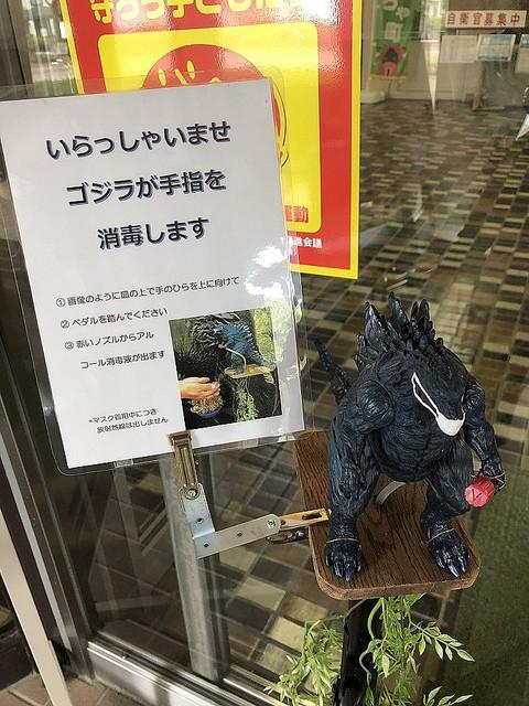 """【放射熱線ではない】北海道の役場に""""アルコール液を吹くゴジラ""""出現足元にあるペダルを踏むことで、ゴジラの手から消毒液が噴霧されるように設計。ゴジラにはマスクが着けられている。"""