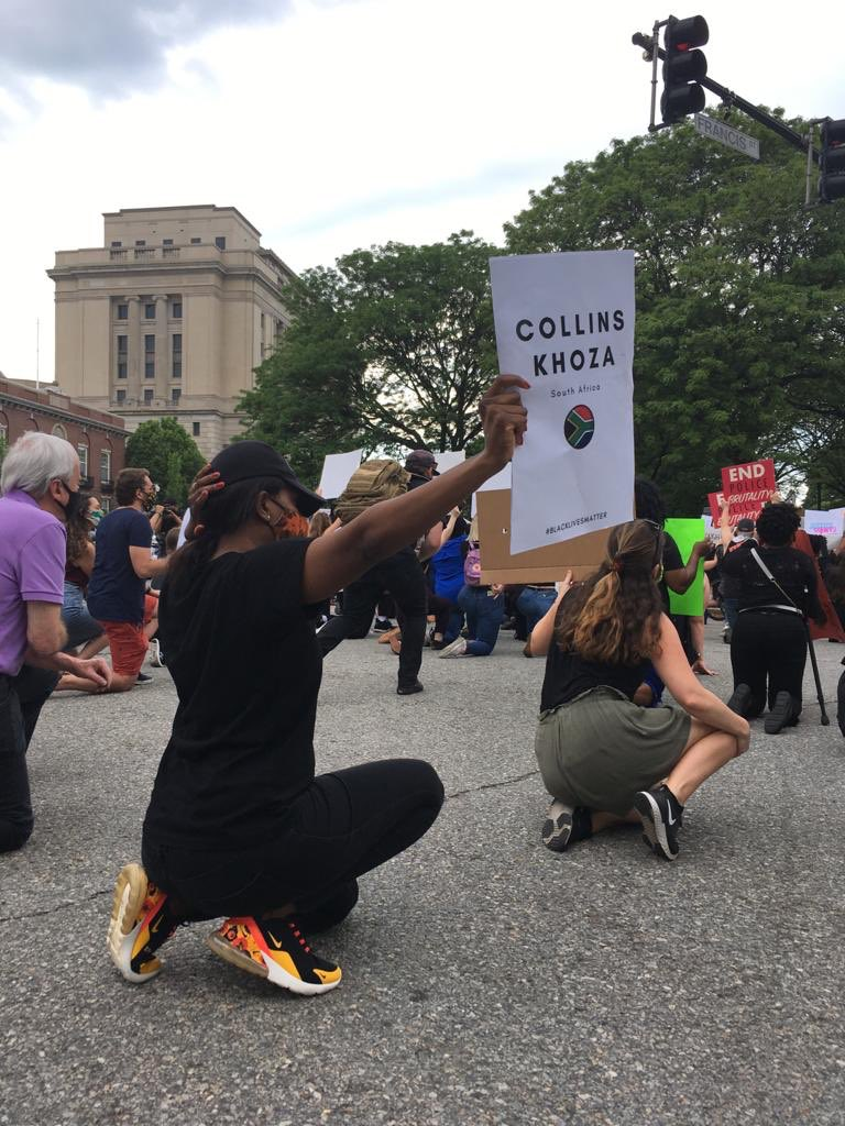 A protester in Providence, Rhode Island, holds up a sign with Collins Khoza's name.
