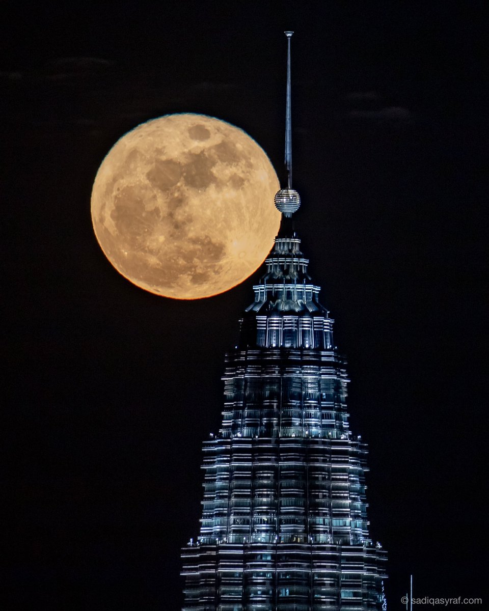 A full moon, also known as the 'Harvest Moon' rises behind Petronas Twin Towers in Kuala Lumpur, Malaysia, to mark the Mid-Autumn Festival on 21 September 2021. - Photo sadiqasyraf.com