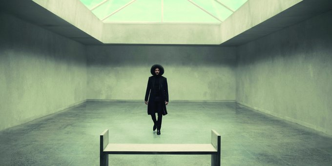 Colin Kaepernick, in a dark and sophisticated outfit, stands in the center of a light grey cement room under a large skylight. A minimalistic bench is in the foreground before him.
