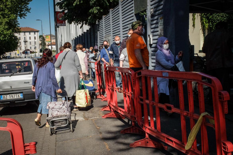 Persone in fila davanti alla Caritas