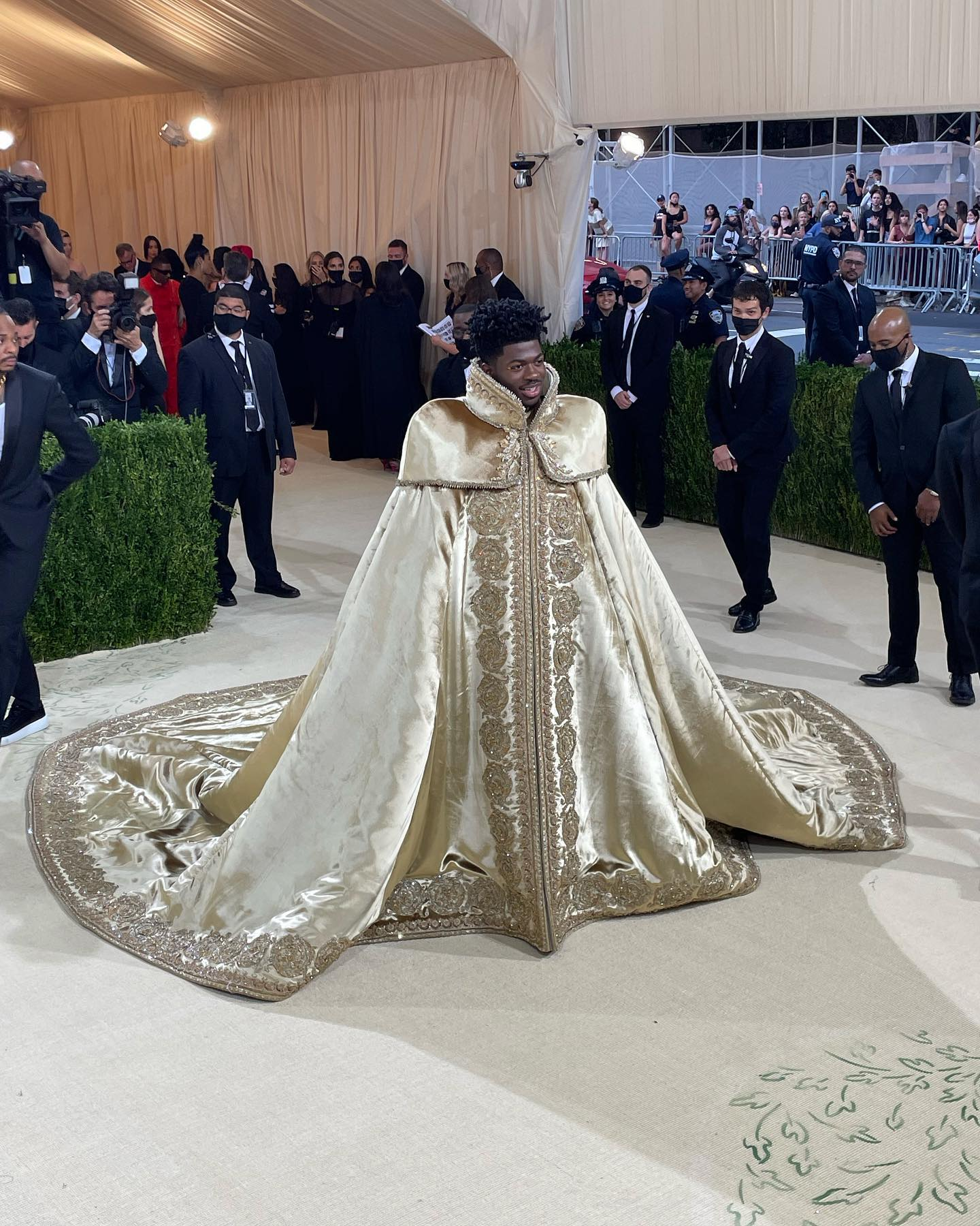 American rapper Lil Nas X stands on The Met's red carpet. He is a dark-skin-toned young man wearing a long, elaborate gold cape, like a royal mantle, with embroidery along its edges and prominent shoulders. Security guards stand in the background.