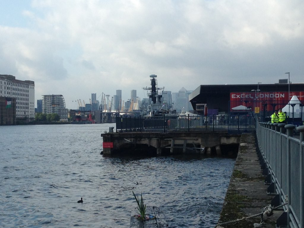 Free Palestine! flag banner drop across the dock from the arms fair #StopArmingIsrael #FreePalestine
