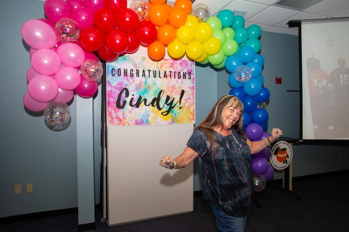 """Persona sonriendo de pie frente al arco de globos de colores del arco iris, que está sobre un letrero de teñido anudado que dice """"¡Felicitaciones Cindy!"""""""