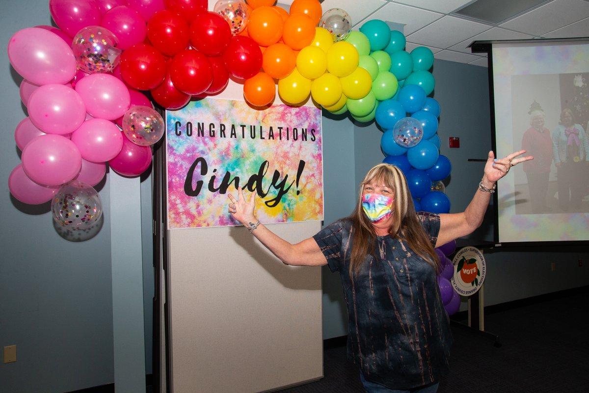 """Persona con máscara de pie frente al arco de globos de colores del arco iris, que está sobre un letrero de teñido anudado que dice """"¡Felicitaciones, Cindy!"""""""