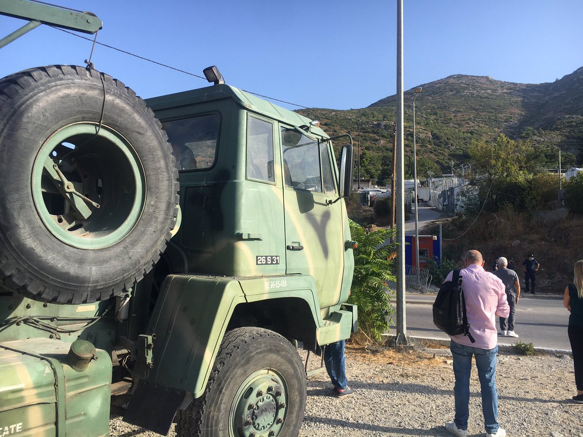 """The transfer of people from the Vathy camp, Samos to the new """"closed controlled"""" refugee camp begins this morning as people bring their belongings down to coaches waiting at the bottom of the camp."""