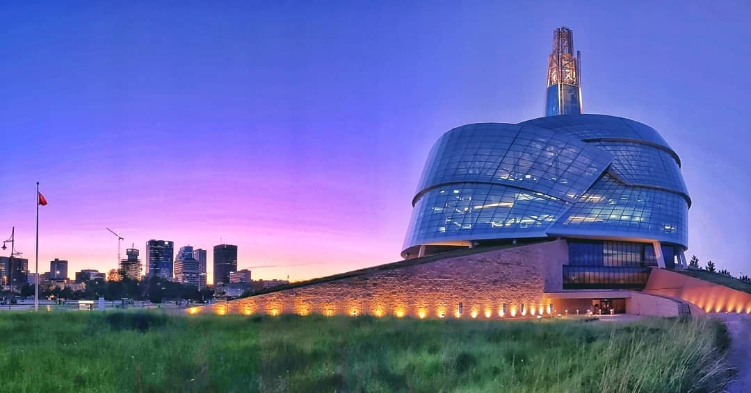 An external shot of the Museum at sunset. The Museum is featured in the foreground to the right of the photo. Winnipeg's downtown skyline is in the background to the left.