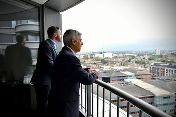 The Mayor of London looking at the skyline from a balcony in one of the newly opened flats.
