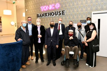 Mayor of London stood in front of the Tonic Bankside sign in a communal area with a group of invited guests.