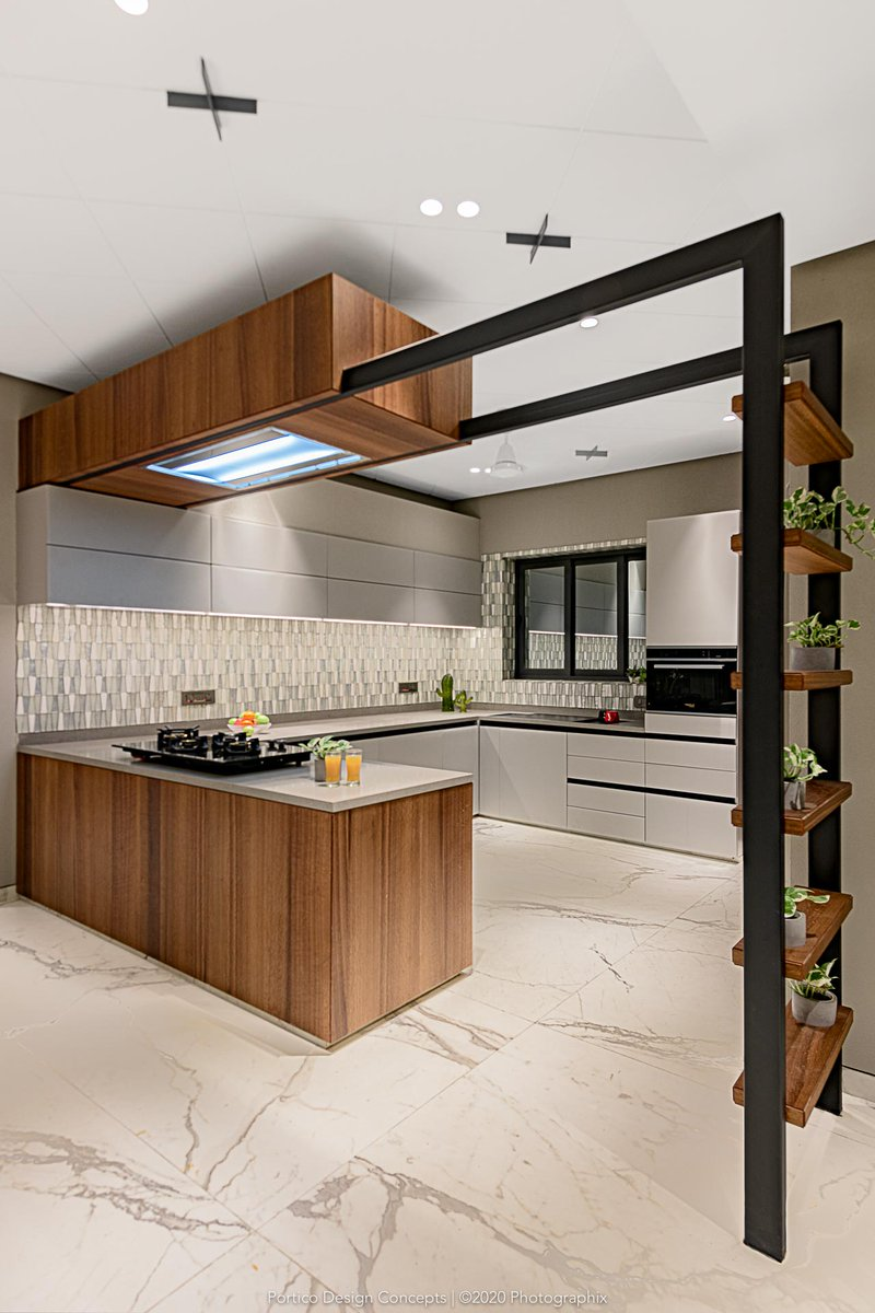 The kitchen at Trivedi House features premium materials such as hand-cut glass mosaic (dado), Caesarstone quartz (countertop) and timber veneers.  #porticodesignconcepts #portico #elevationdesign #insideoutside #Homedesign #TheChampionHouse