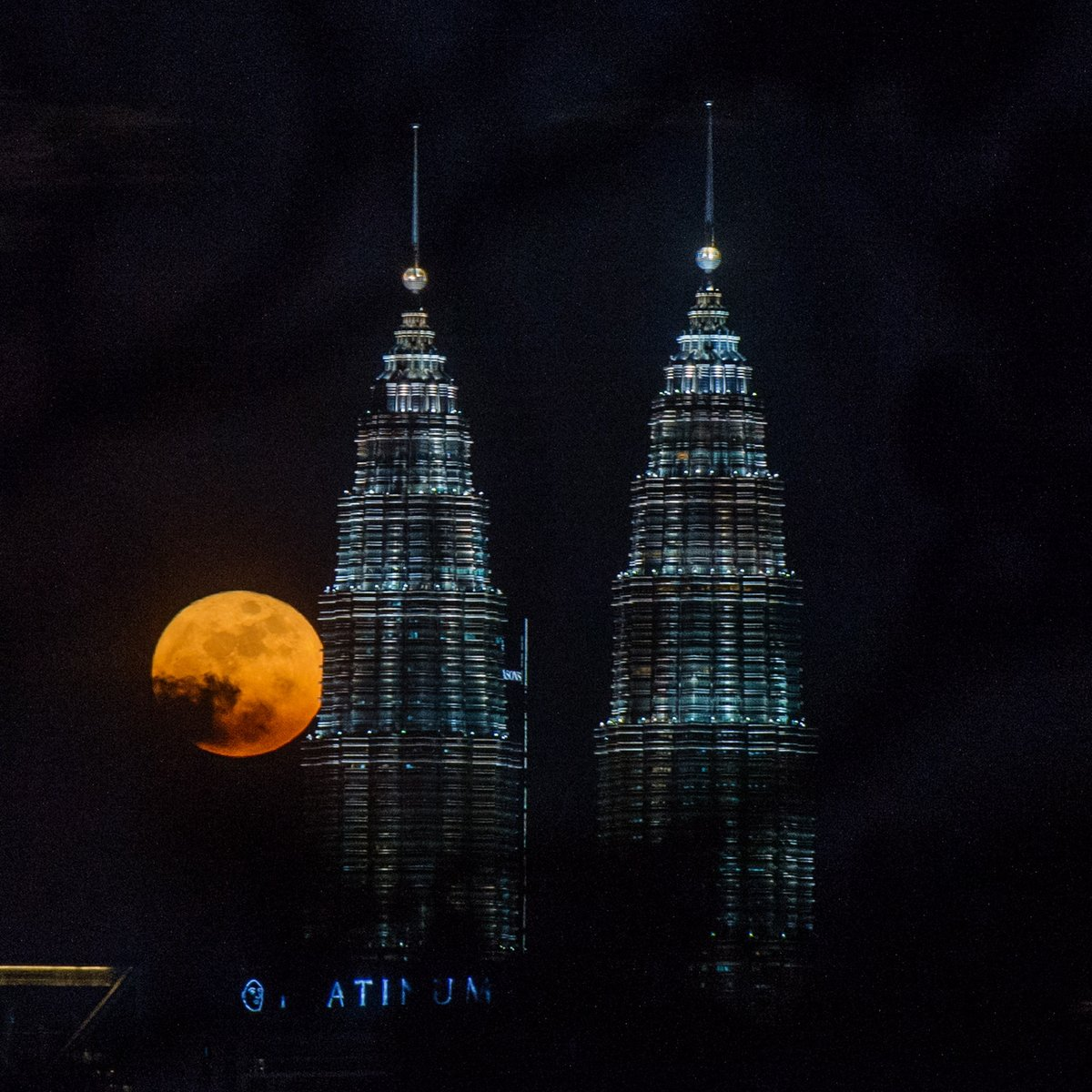 Full moon seen between Petronas Twin Towers (KLCC) during mid-autumn festival in Kuala Lumpur, September 21, 2021. On the 15th of each lunar calendar month, the moon is at its roundest and brightest, symbolizing togetherness and reunion in Chinese culture.
