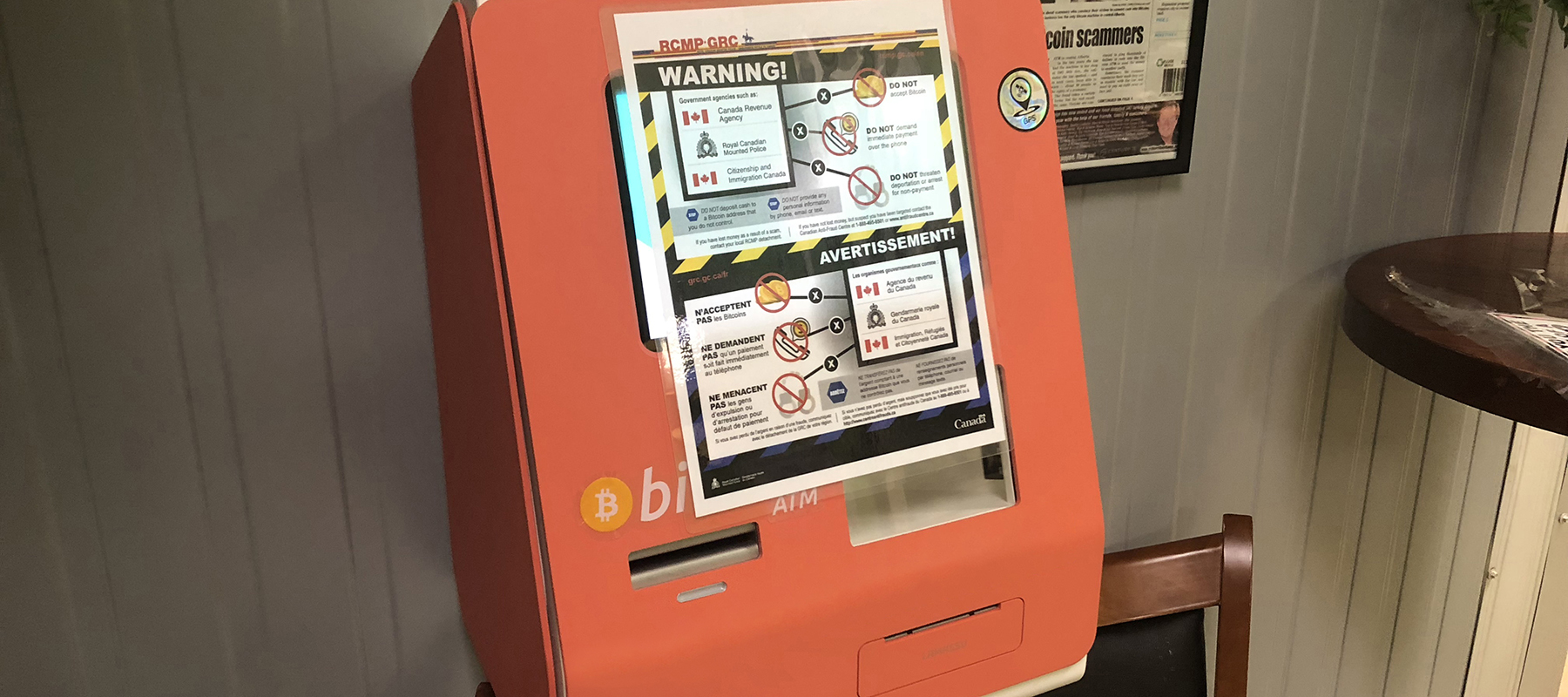 A bilingual warning poster taped to a Bitcoin ATM.