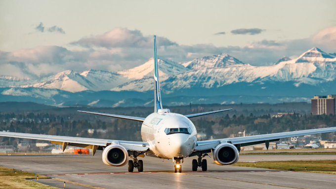 WestJet aircraft with rocky mountains in the distance