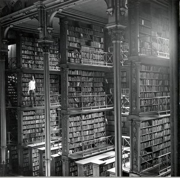 A man browsing for books in Cincinnatis cavernous old main library. The library was demolished in 1955.